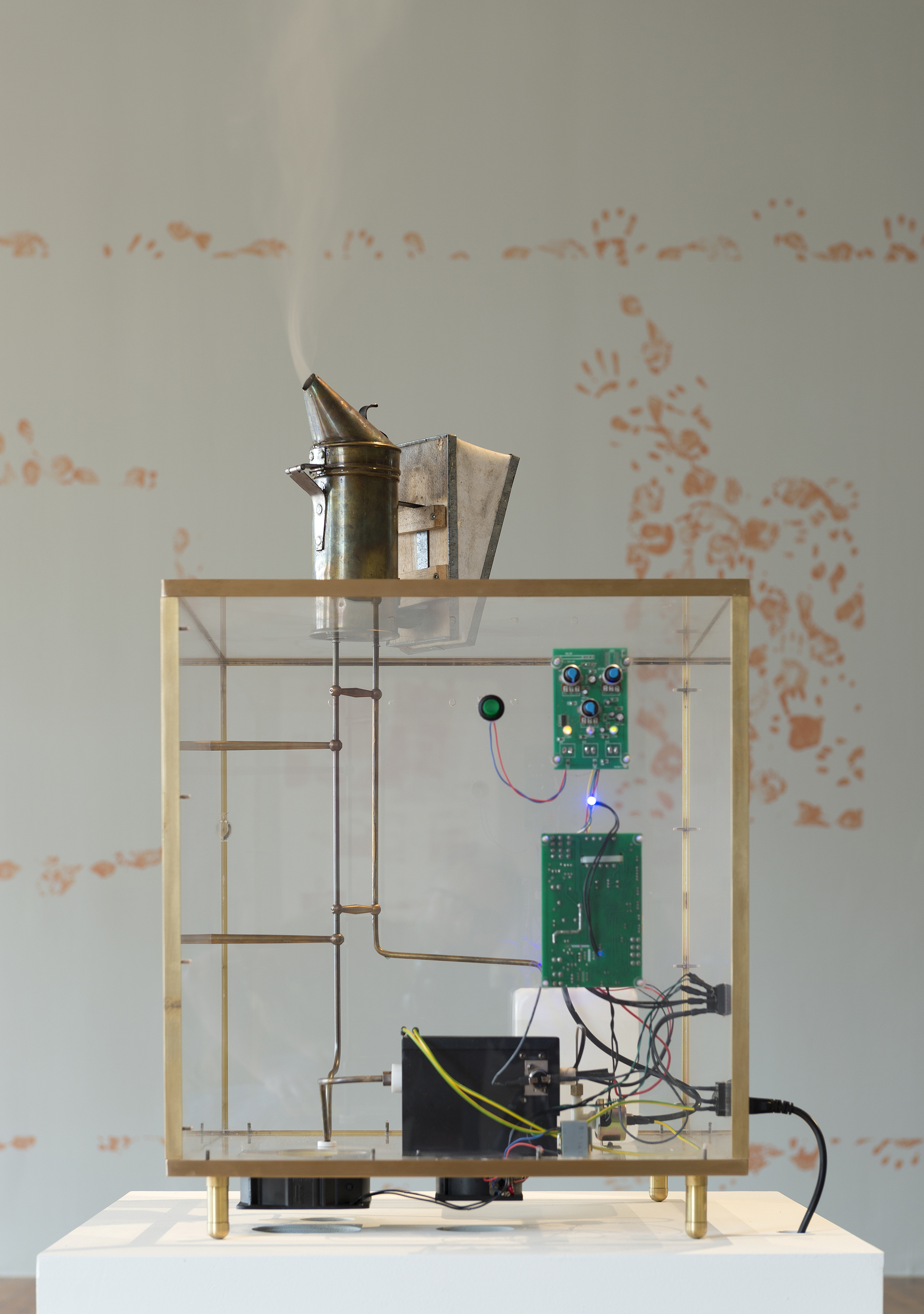 Francisco Tropa,  Fumeux fume, 2018. Eléments en laiton, plexiglas, machine à fumer, enfumoir, 82 x 50 x 50 cm. Production Le Grand Café - centre d'art contemporain, vue de l'exposition Le Grand Café, la Moustache cachée dans la barbe, 2018. Courtesy Galerie Jocelyn Wolff, Paris. Photographie Marc Domage.